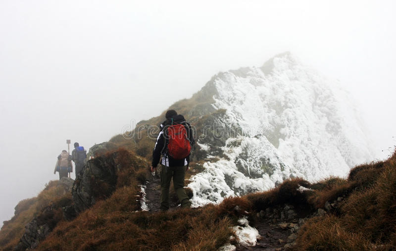 Escaladores que descienden de las montañas de Fagaras en el mún tiempo foto de archivo