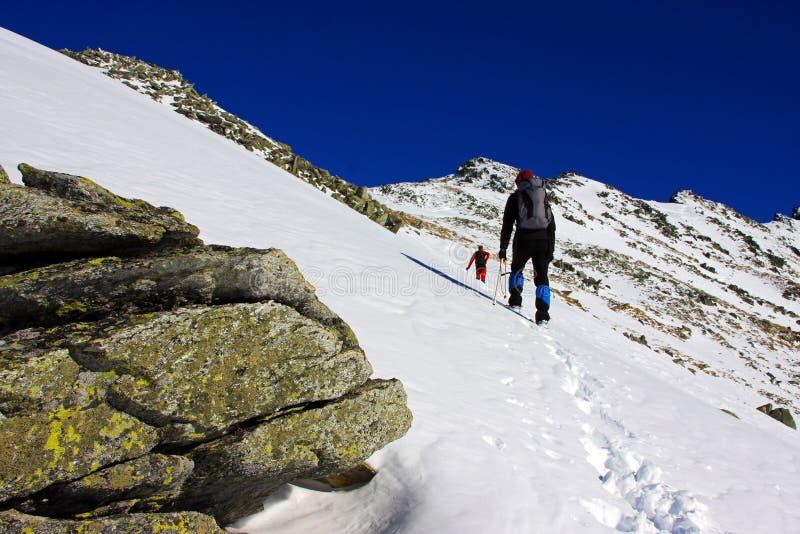 Escaladores que van para arriba la montaña en las montañas de Retezat, Rumania imagenes de archivo