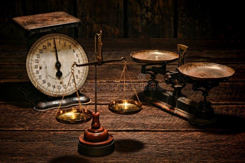 Escalas antigas do equilíbrio na tabela velha da madeira da loja imagem de stock