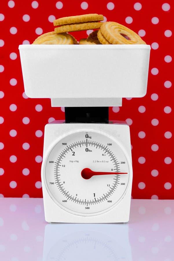 Escalas de la cocina con concepto de la dieta de las galletas fotos de archivo