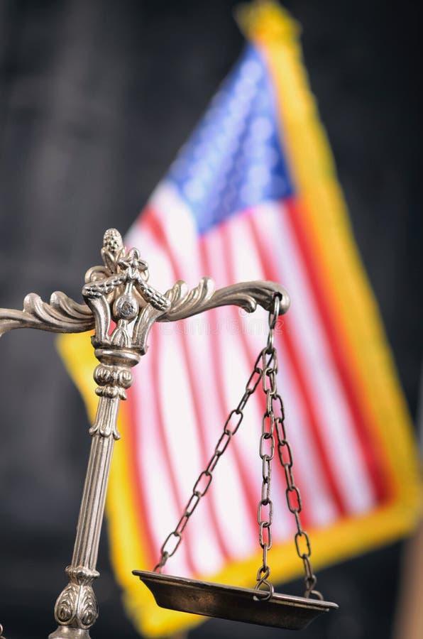 Escalas de la justicia delante de la bandera americana en el fondo foto de archivo