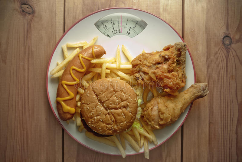 Escalas de peso da dieta de comida lixo foto de stock