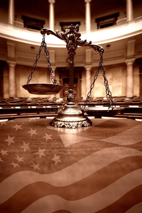 Escalas decorativas de la justicia en la sala de tribunal y la bandera americana fotografía de archivo libre de regalías