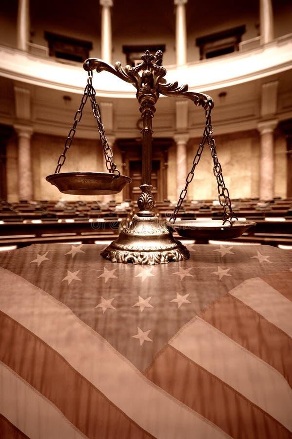 Escalas decorativas de la justicia en la sala de tribunal y la bandera de los Estados Unidos imágenes de archivo libres de regalías