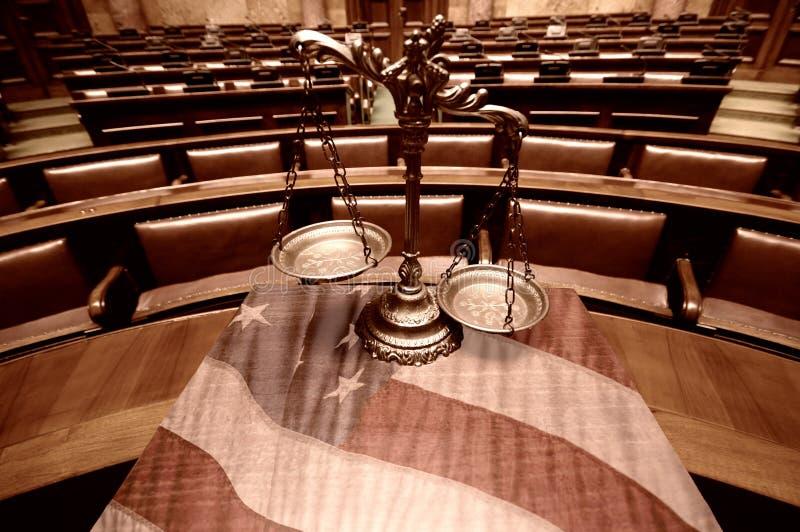 Escalas decorativas de la justicia en la sala de tribunal y la bandera de los Estados Unidos imagen de archivo libre de regalías