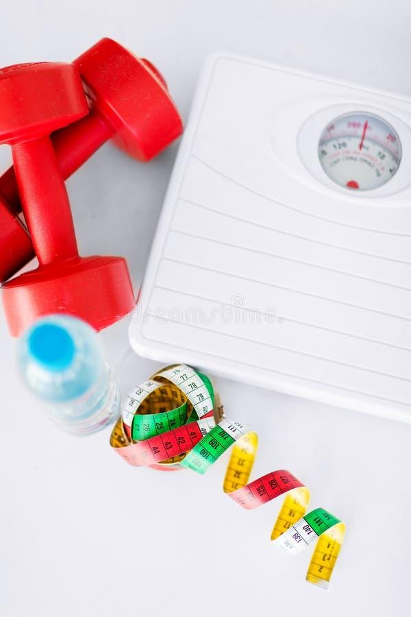 Escalas, pesas de gimnasia, botella de agua, cinta métrica imagen de archivo libre de regalías