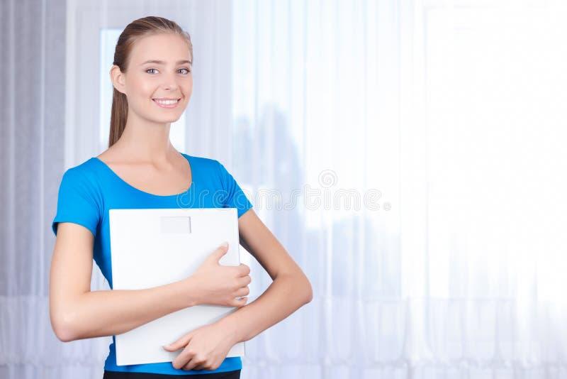 Escalas sonrientes de la tenencia de la chica joven imagen de archivo libre de regalías