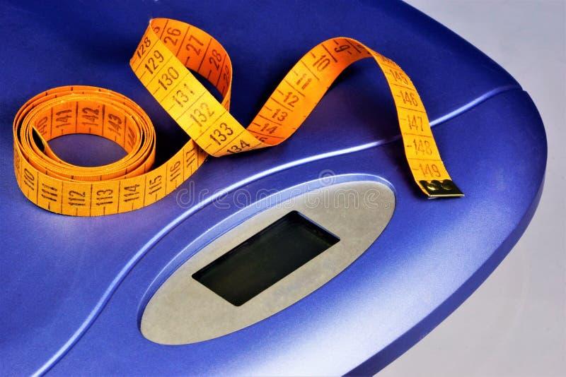 Escalas y figuras del centímetro-control, peso en aptitud Obesidad, gestión del peso y consumición sana La figura atractiva es imagenes de archivo