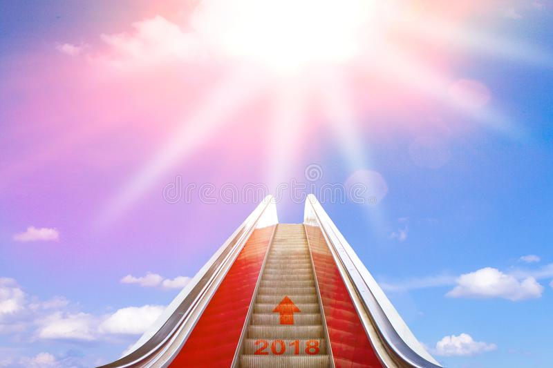 Escalator bright sun light 2018. Ascending on an escalator with an arrow and 2018 written on it into sunlight. Concept photo for a successful new year and a stock photography