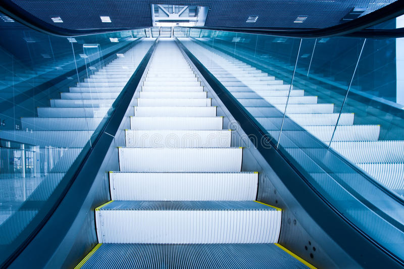 Escalator dans le couloir bleu photos stock