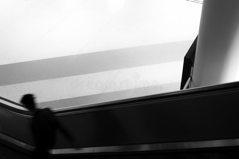 Escalator with person in motion blur at bus terminal in dark black and white. royalty free stock image