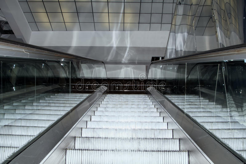 Escalator stairs moving up in modern office building royalty free stock images