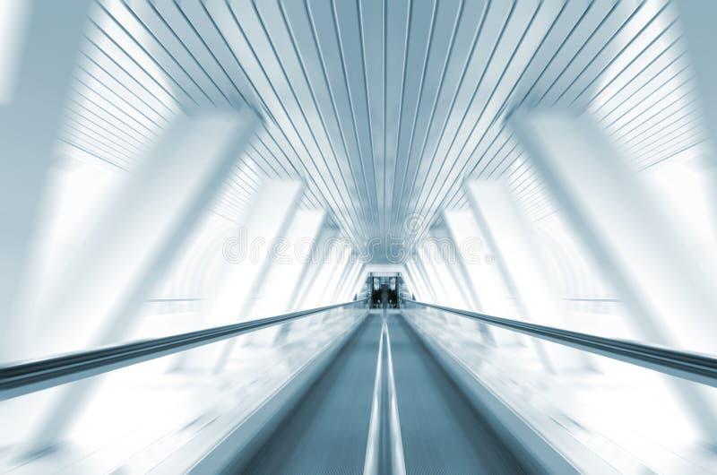Escalator in symmetrical glass corridor stock image