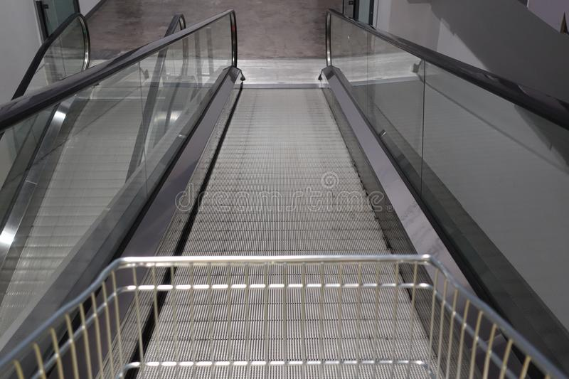 Escalator for trolley shopping car in depart meant store for customer use in case. They have a lot of products stock photos