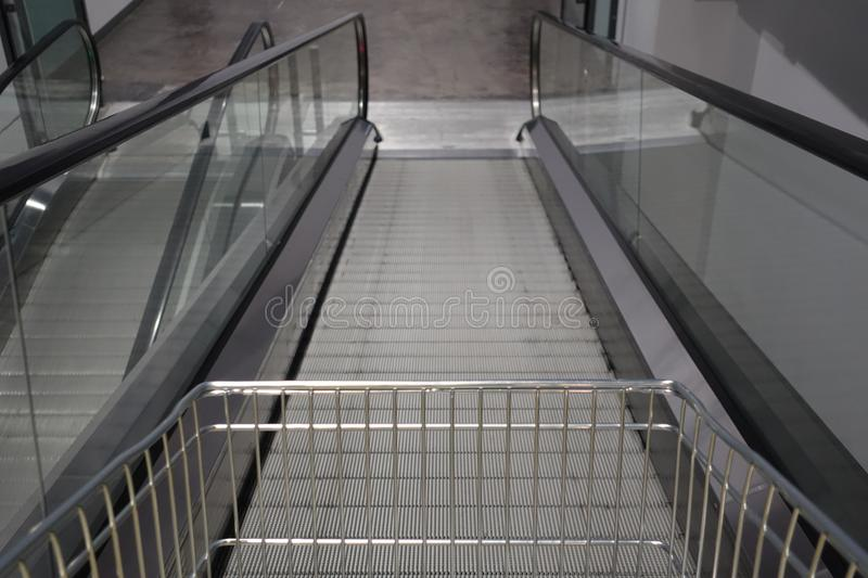 Escalator for trolley shopping car in depart meant store for customer use in case. They have a lot of products royalty free stock image