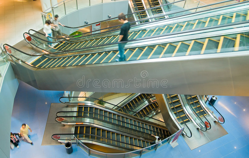 Escalators. Moving up and down in all directions at all levels in a modern high rise mall royalty free stock photos