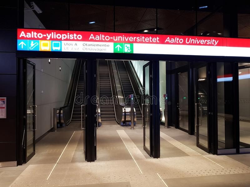 Escalators, doors and info sign at the platform entrance of new Aalto University metro station. ESPOO, FINLAND - DECEMBER 17, 2017: Escalators, doors and info royalty free stock photos