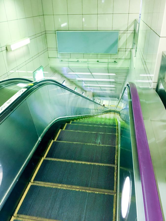 Escalators facilities leading down into a Subway Station with Neon Lights, Moving Staircase. Modern luxury escalators facilities leading down into a Subway royalty free stock photo
