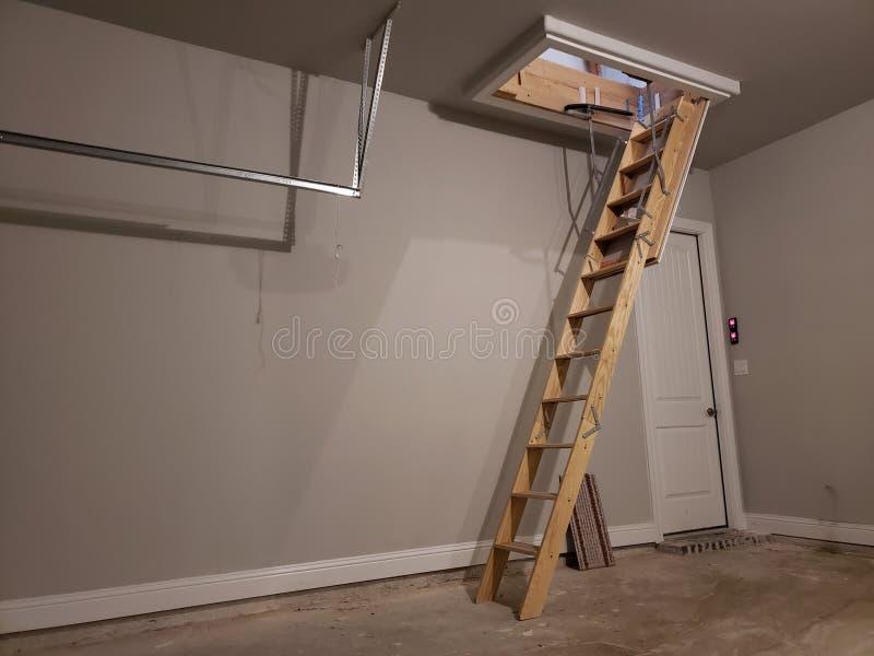 Escalera al ático en garaje de una nueva casa fotografía de archivo