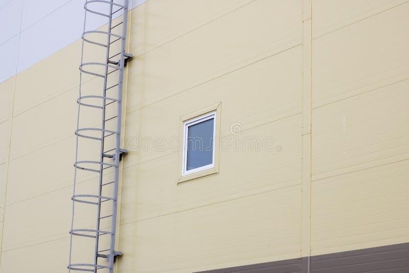 Escalera al tejado de un edificio alto y a la ventana en un fondo oscuro del cielo imagen de archivo