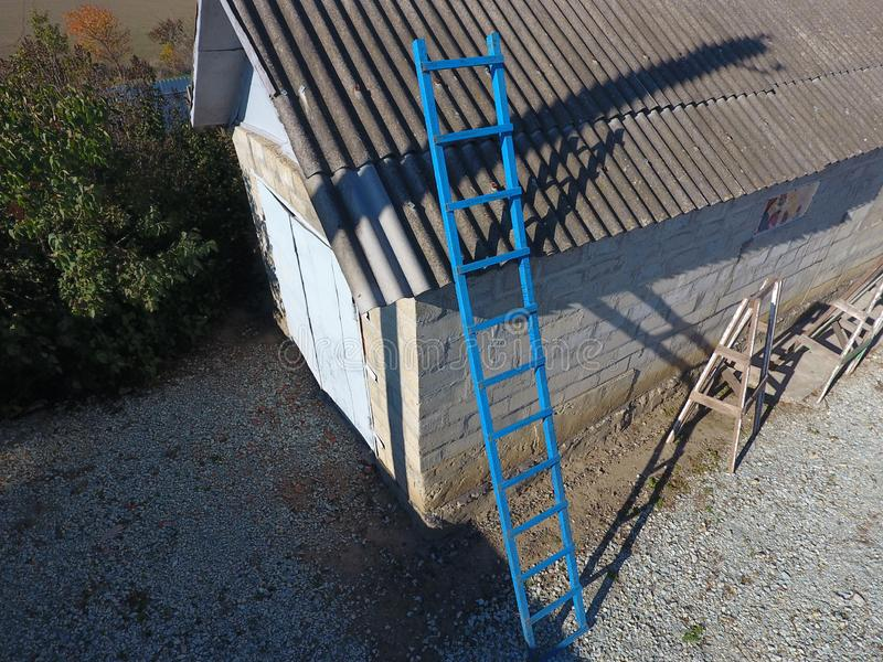 Escalera azul de acero al tejado del granero Escalera de un metalprofile fotografía de archivo