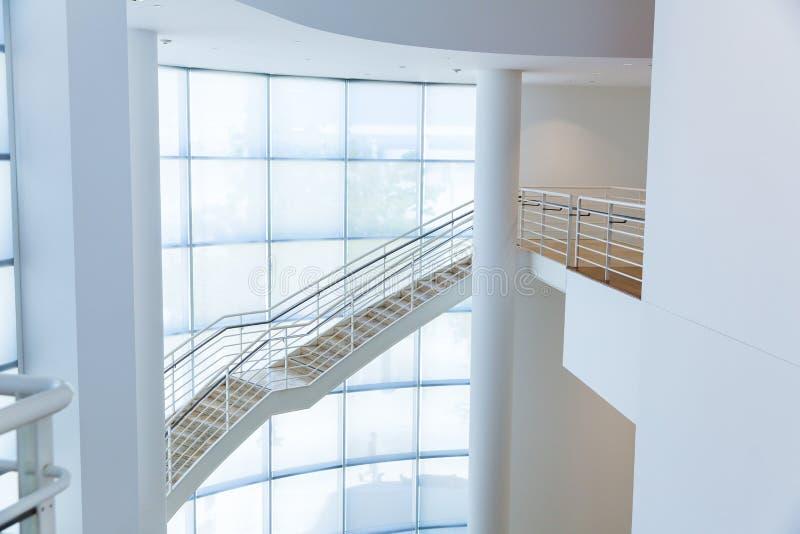 Escalera con las barandillas del metal contra la pared de cristal imagen de archivo