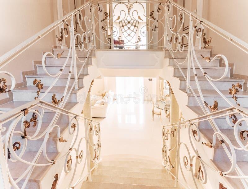 Escalera con los pasos de mármol y con la barandilla ornamental del hierro foto de archivo
