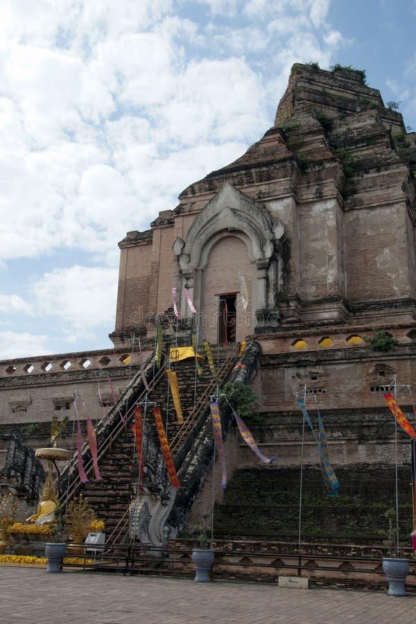 Escalera de la entrada con la estatua de Buda y banderas en Wat Chedi Luang foto de archivo libre de regalías