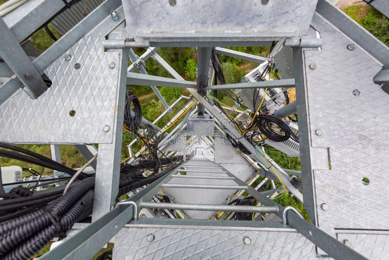 Escalera de la portilla y del metal en la torre de la telecomunicación y antenas instaladas con el equipo de telecomunicación al  imagen de archivo