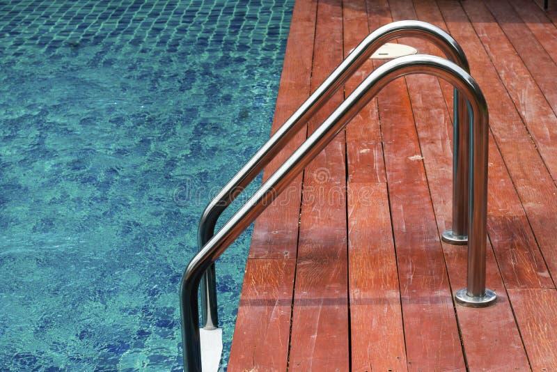 Escalera de las barras de gancho agarrador en la piscina azul imagenes de archivo