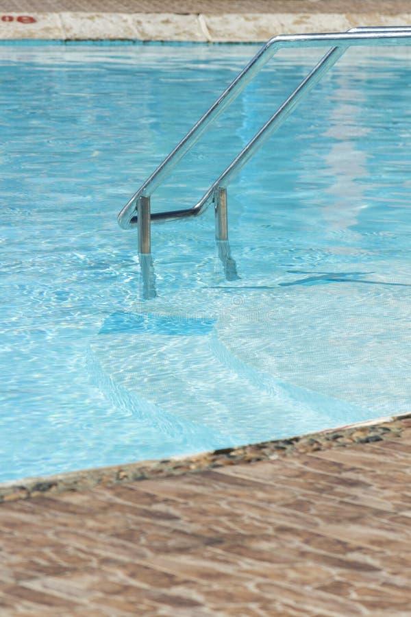 Escalera de las barras de gancho agarrador en la piscina azul Lado curvado de una piscina con las escaleras Foto vertical imagenes de archivo