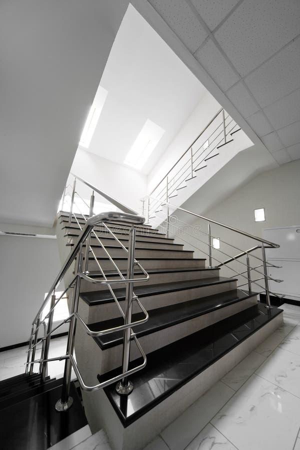 Escalera de mármol con una barandilla de acero foto de archivo
