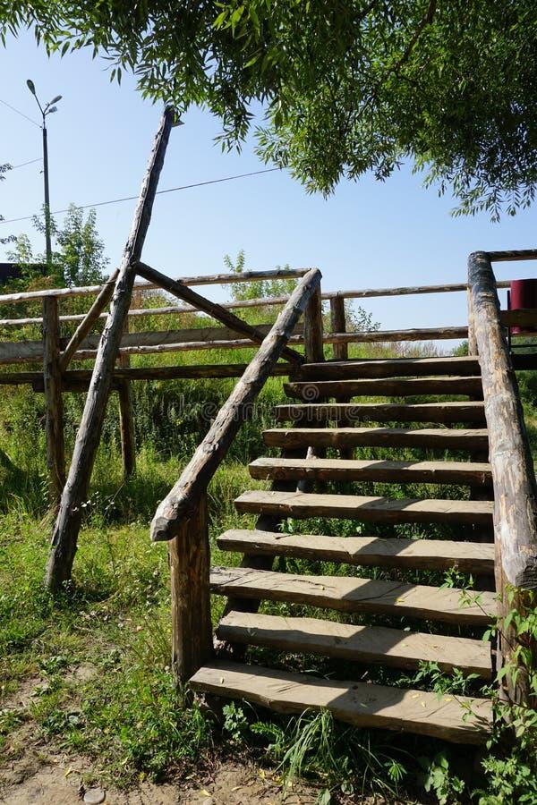 Escalera de madera con la verja áspera de registros fotos de archivo