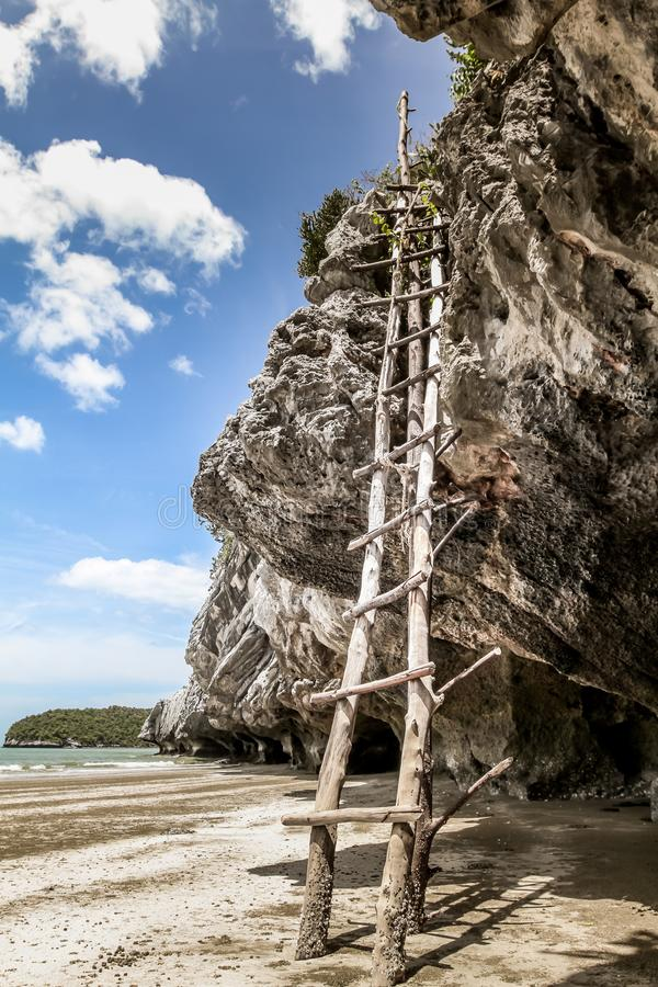 Escalera de madera a subir hasta la roca en la playa con playa y el cielo nublado azul en el fondo fotos de archivo libres de regalías