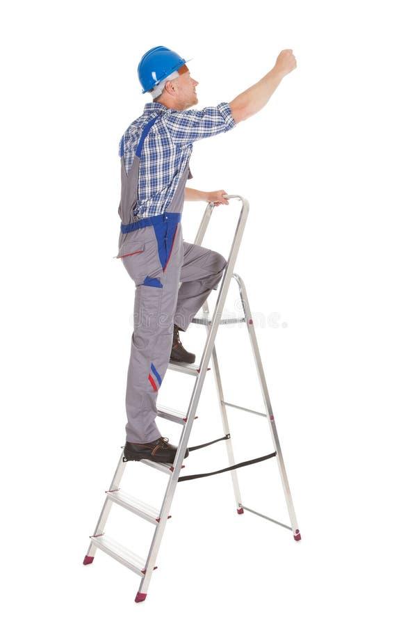 Escalera de paso del reparador que sube fotografía de archivo libre de regalías