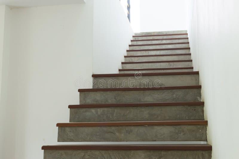 Escalera del cemento y de madera en la pared blanca del Modelos de escaleras de cemento