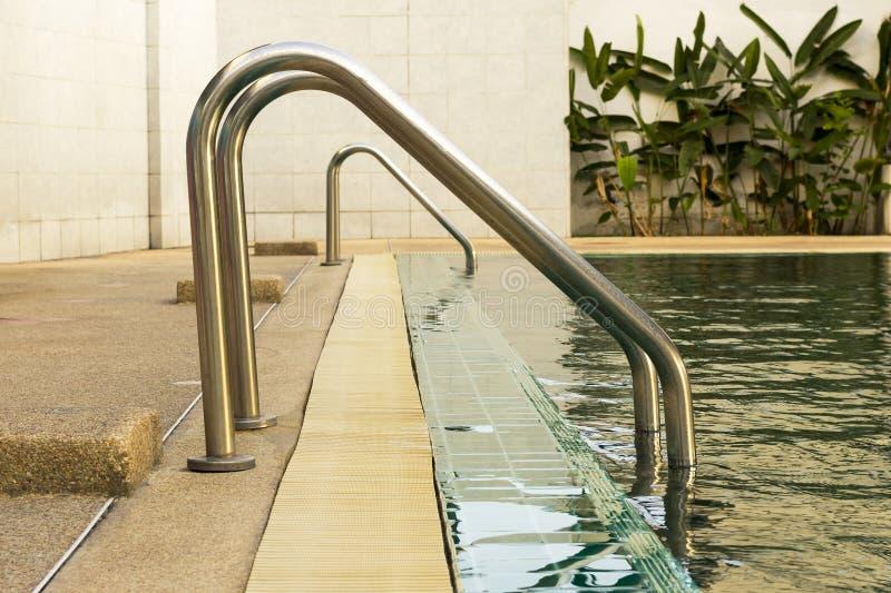 Escalera del metal en piscina de la escuela con reflexiones soleadas foto de archivo
