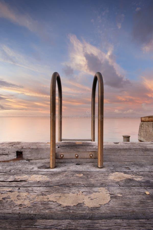 Escalera en el embarcadero en la puesta del sol de la salida del sol foto de archivo libre de regalías