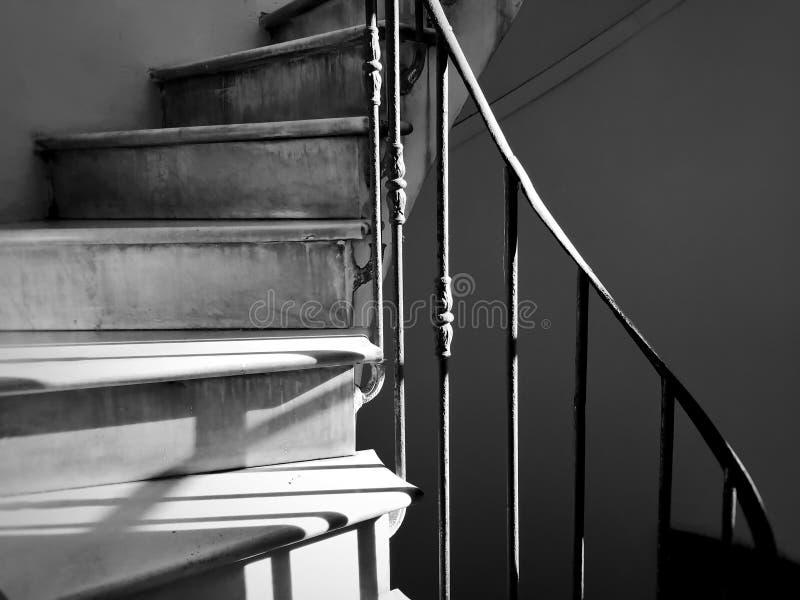 Escalera espiral antigua con la barandilla adornada del hierro imágenes de archivo libres de regalías
