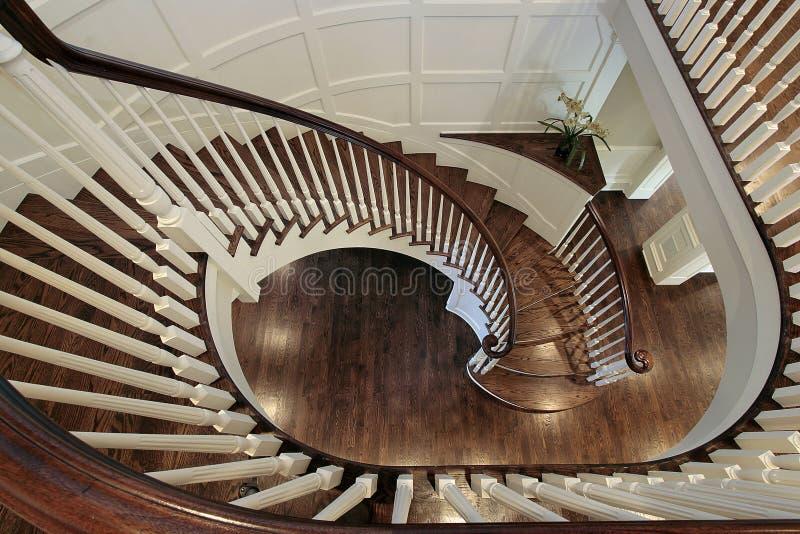 Escalera espiral con el pasamano de madera fotografía de archivo