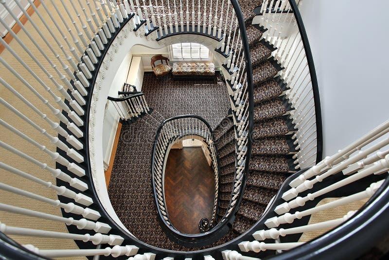 Escalera espiral con el pasamano negro fotos de archivo