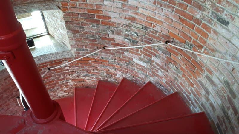 Escalera espiral con la ventana, escaleras rojas, pared de ladrillo imagen de archivo