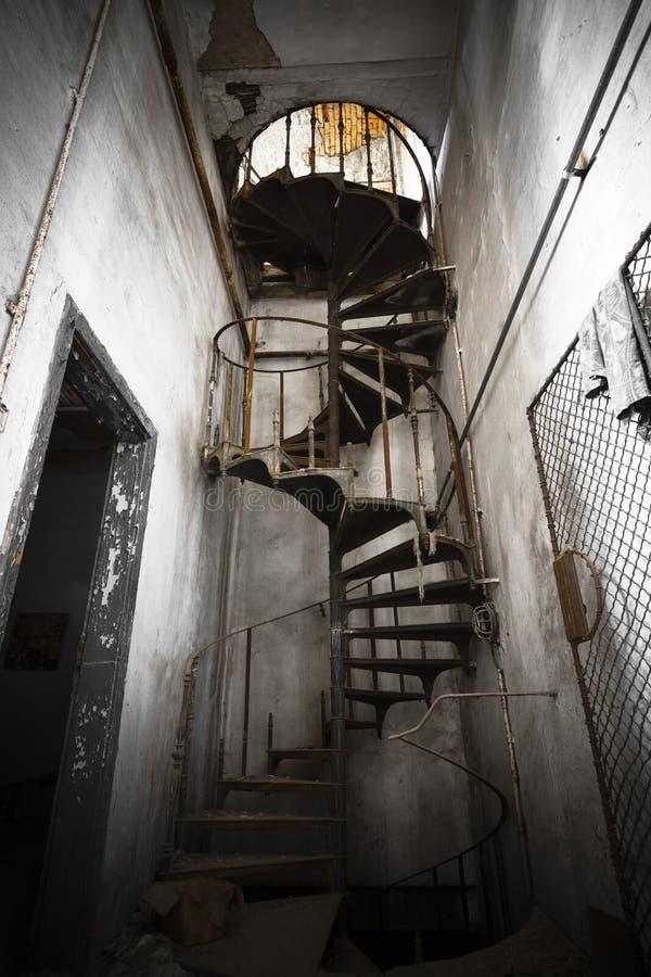 Escalera espiral en un edificio abandonado de la fábrica imágenes de archivo libres de regalías