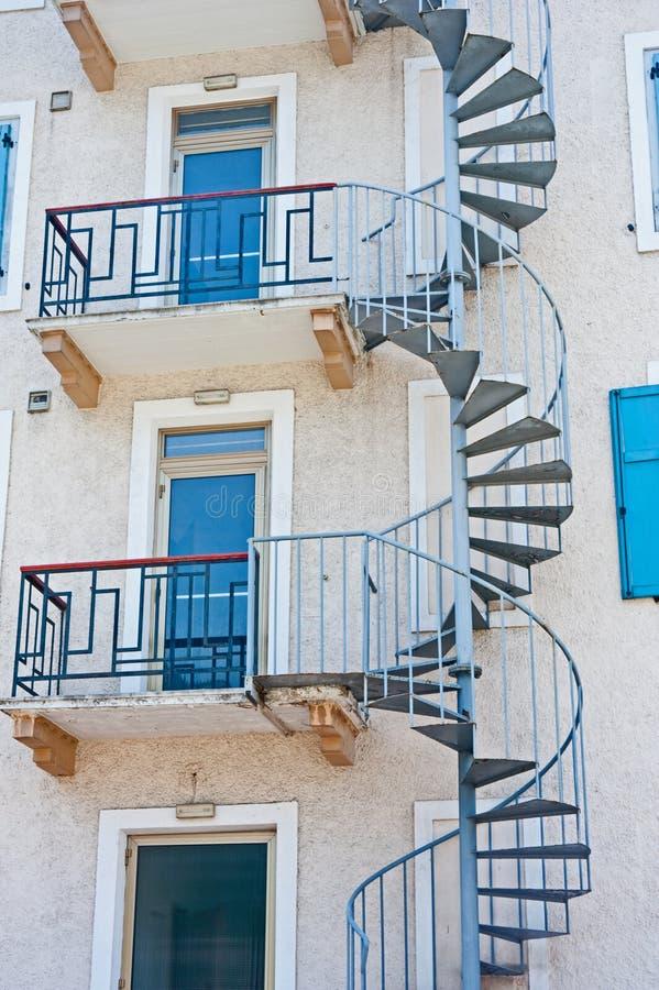 Escalera espiral que lleva a las puertas azules fotos de archivo