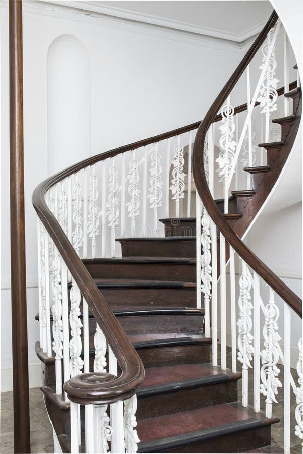 Escalera espiral vieja con las escaleras de madera imagen de archivo