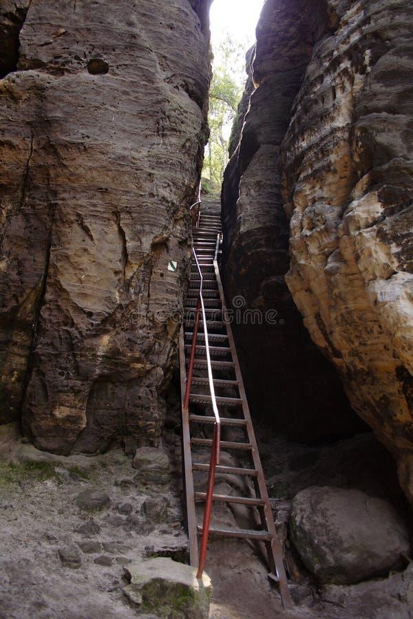 Escalera estrecha del hierro por la piedra imagen de archivo libre de regalías