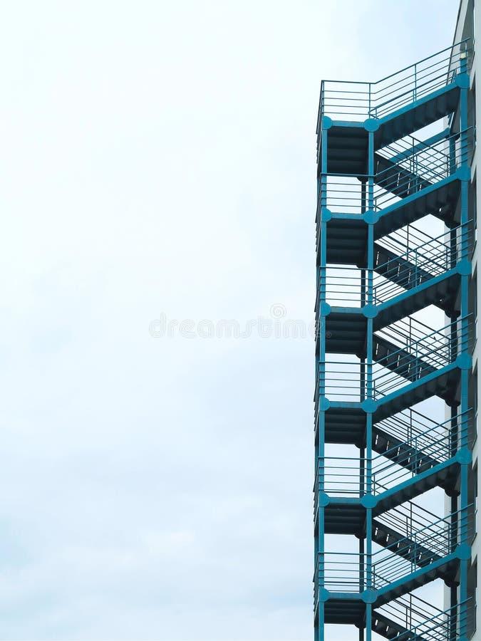Escalera exterior verde de las escaleras de la salida de incendios sobre el cielo nublado imagenes de archivo