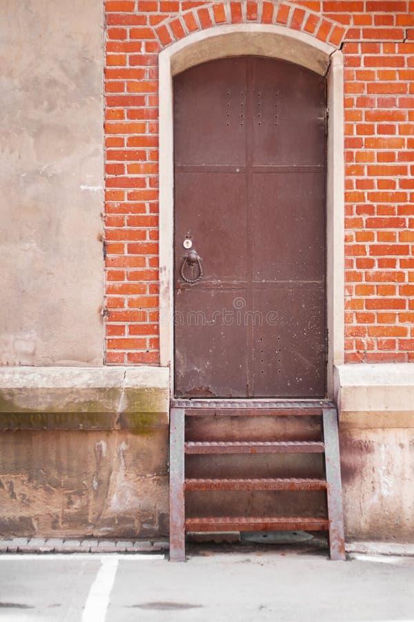 Escalera a la puerta oxidada cerrada vieja del metal en pared de ladrillo roja Imagen urbana e industrial Vertical con el espacio foto de archivo libre de regalías