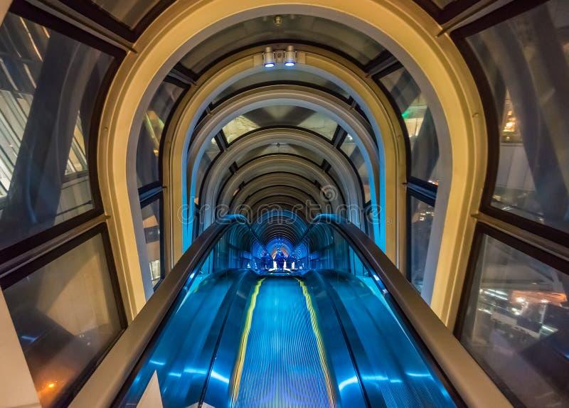 Escalera móvil de cristal moderna del túnel entre dos edificios fotografía de archivo libre de regalías