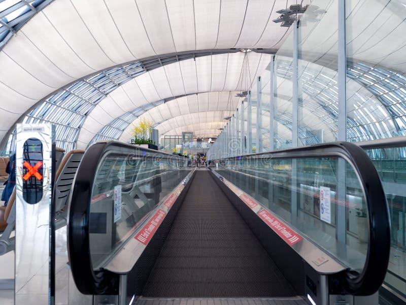 Escalera m?vil del aeropuerto en la b?veda de un alto tejado